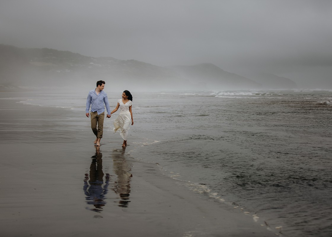 Couple strolling at Auckland Beach,